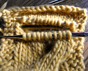 pullout the cabled stitches, place on needles and re-knit properly